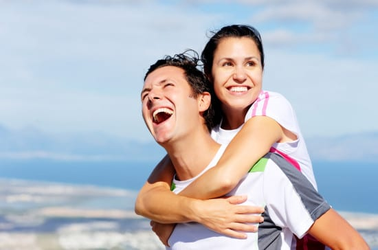 Happy couple embrace each other and laugh together outdoors in a healthy relationship outdoors concept