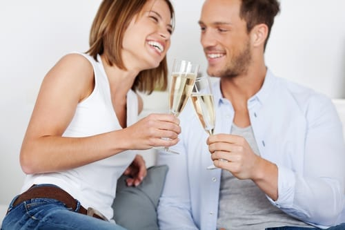 Laughing young couple dating with champagne at home